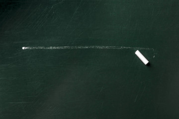 A photo of a line with a piece of chalk on a dark blackboard with copy space