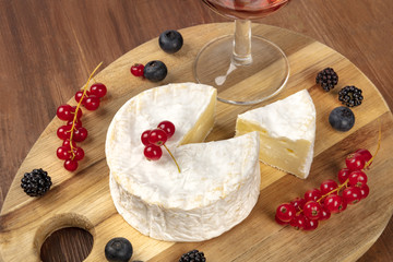 A photo of Camembert cheese with a glass of red wine and fruits, on a dark rustic background with copy space