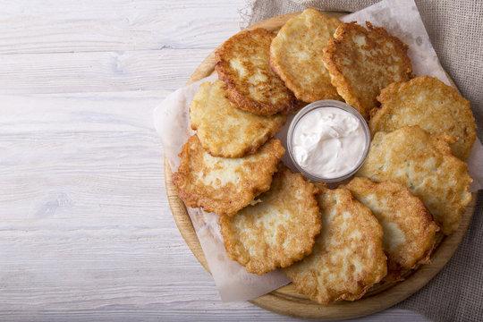 Golden potato pancakes with sour cream. Top view. Copyspace