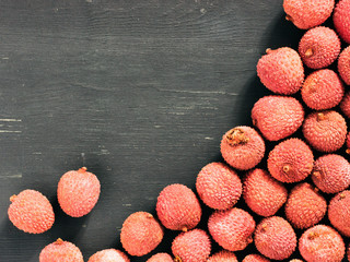 lichee fruit on dark wooden background close up with copy space. Top view or flat lay