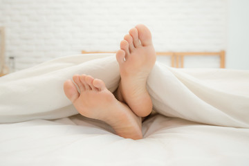 Close up two feet of woman sleep on white bed in bedroom,Feeling relax and comfortable,Healthcare Concept