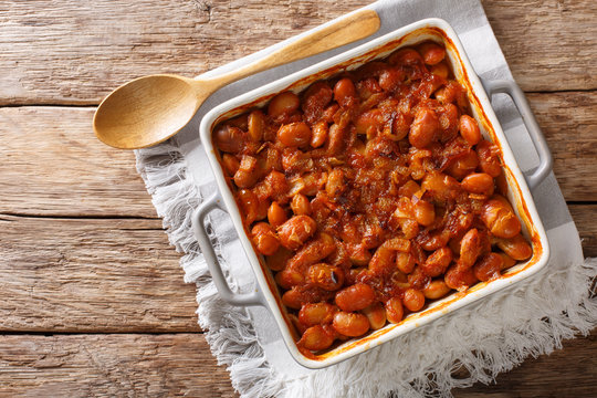 Baked spicy beans prebranac close-up in a baking dish. Horizontal top view from above