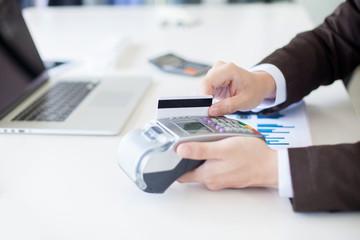 Businessman hand with credit card swipe through terminal