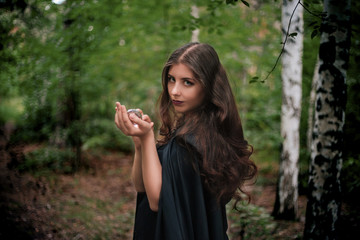 A woman in a black cloak is holding a crystal ball in her hands. Forest predictor of the future, witch.