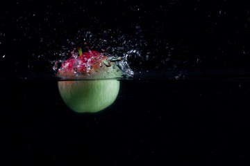 green red apple half fallen into the water formed a splash
