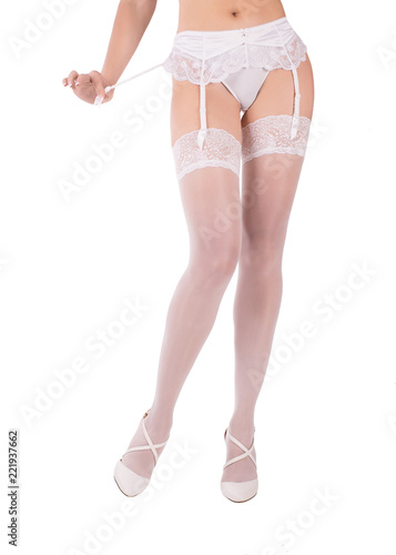 07bcaac64e6 Sexy female legs and body in white garter belt, lace stockings, panties and  white shoes, bride style. Isolated on white