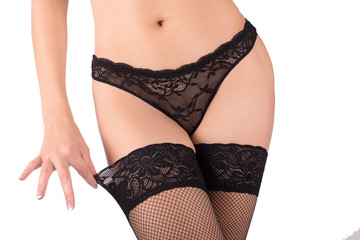 Female body in black sexy fishnet stockings and lace panties. Close up, isolated on white
