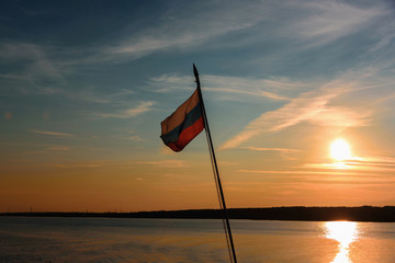 Russian flag flies on the flagpole at sunset against the backdrop of the river and sky. Freedom is independence and patriotism.