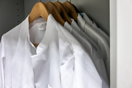 White smocks on wooden hangers hang in the cupboard of a laboratory