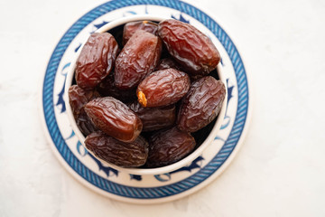 Fresh Medjool Dates in a bowl. Ramadan kareem. White background. Turkish style. Top view. Copy space.