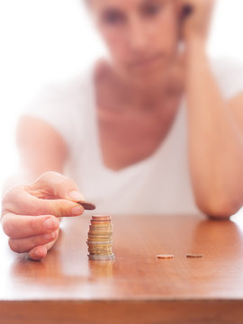 Mature older woman putting coins into a pile, heap, on table. Defocussed high key background. Poverty concept, counting pennies, small change. Euros.