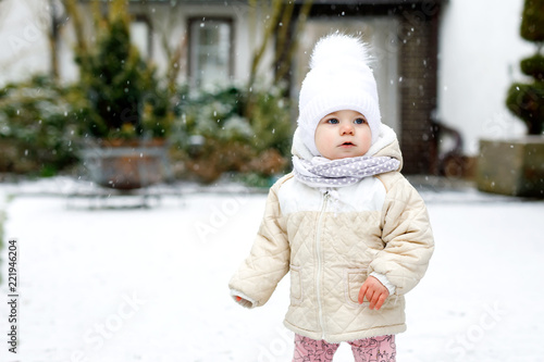 9b3aa5601 Adorable little baby girl making first steps outdoors in winter ...
