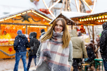 Beautiful young woman having fun on traditional German Christmas market during strong snowfall.