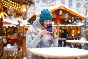 Beautiful young woman drinking hot punch, mulled wine on German Christmas market. Happy girl in winter clothes with lights on background on winter snow day in Munich, Germany.