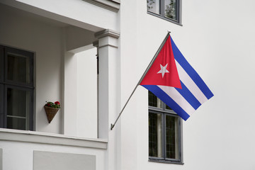 Cuba flag.  Cuba flag hanging on a pole in front of the house. National flag of waving on a home displaying on a pole on a front door of a building. Flag raised at a full staff.