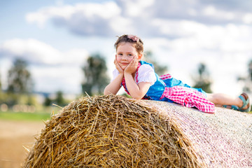 Cute little kid girl in traditional Bavarian costume in wheat field. German child with hay bale during Oktoberfest in Munich. Preschool girl play at hay bales during summer harvest time in Germany.