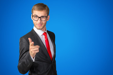 Young handsome businessman pointing on you