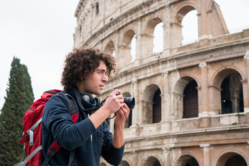 Handsome young tourist man with a camera and backpack taking pictures of Colosseum in Rome, Italy. Young tourist taking pictures of Colosseum