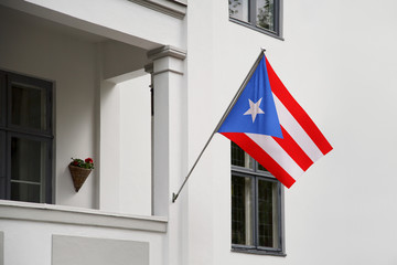 Puerto Rico flag. Puerto Rican flag hanging on a pole in front of the house. National flag of waving on a home displaying on a pole on a front door of a building. Flag raised at a full staff.