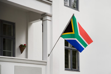 South Africa flag. South African flag hanging on a pole in front of the house. National flag of waving on a home displaying on a pole on a front door of a building. Flag raised at a full staff.