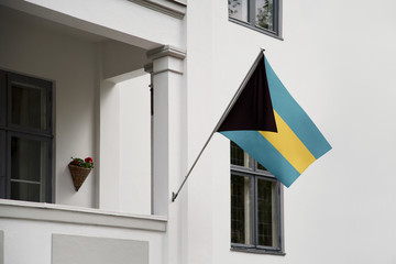 Bahamas flag.  Bahamas flag hanging on a pole in front of the house. National flag of waving on a home displaying on a pole on a front door of a building. Flag raised at a full staff.