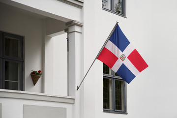 Dominican Republic flag.  Dominican Republic flag hanging on a pole. National flag waving on a home displaying on a pole on a front door of a building. Flag raised at a full staff.