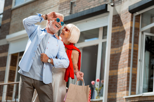 Full of emotions. Positive fashionable elderly couple having pleasant walk after shopping while keeping their purchases in hands