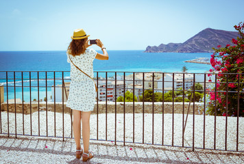 Tourist girl with straw sunhat taking a picture of the mediterranean sea with a smartphone in Altea, Alicante, Spain