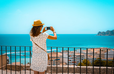 Tourist girl with straw sunhat taking a picture of the mediterranean sea with a smartphone in Altea, Alicante, Spain. Orange and teal style