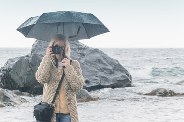 A female photographer with an umbrella from the rain makes a photo on the stony coast of the sea, the ocean. Photographing in all weather conditions.
