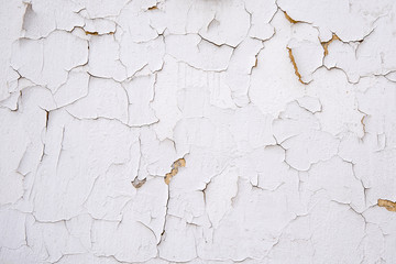 Cracks in the white old plaster . Background for a variety of interesting materials.