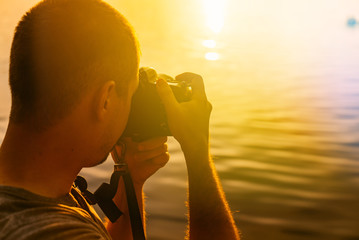 a man takes a picture of sunset by the river. Close-up