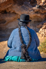 Old bolivian woman in traditional outfit with a hat and long braids