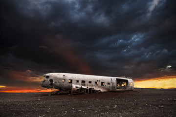 wreck of a white airplane on the black beach Wall mural