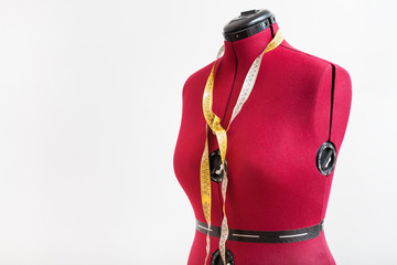 red dress form with measuring tape in workshop