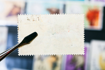 tongs holds postage stamp with unused back side