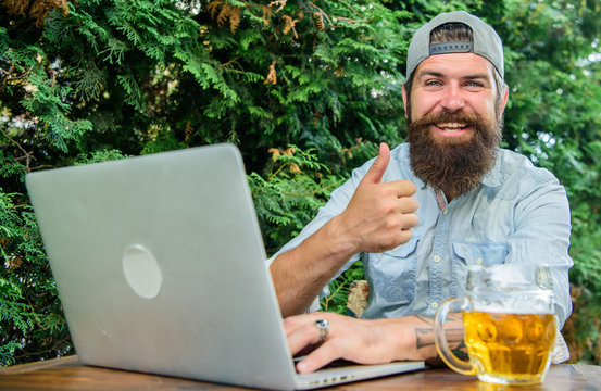 Football fan bearded hipster make bet sport game laptop. Guy sit terrace outdoors with beer. Betting and real money gaming. Brutal man leisure with beer and sport game. Bet on world championship