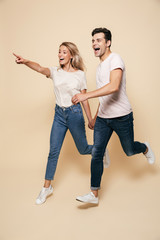Happy young loving couple walking isolated over beige wall background pointing.