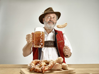 Germany, Bavaria, Upper Bavaria. The senior happy smiling man with beer dressed in traditional Austrian or Bavarian costume holding mug of beer at pub or studio. The celebration, oktoberfest, festival
