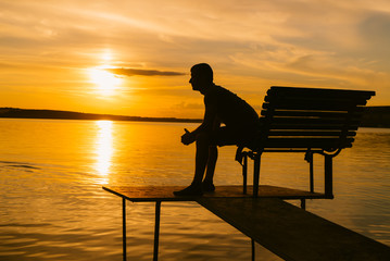adult man sits on the bench with folded hands on the background of river at sunset