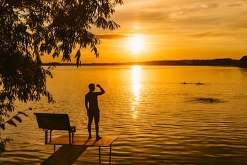 a man stands on a masonry near the lake and looks at the sunset. People bathe in the lake in the...