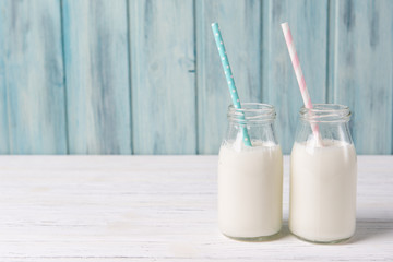 Two bottles of milk with straws, wooden background