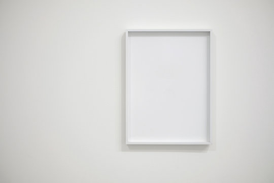 Empty white frame on white wall for interior decoration. Minimal concept