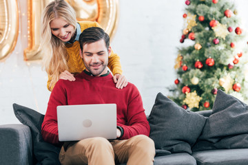 happy couple using laptop together at home on christmas