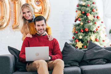 smiling couple using laptop together at home with christmas tree