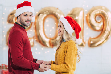 05e7184b4db82 smiling couple in santa hats holding hands at home with 2019 new year  golden balloons