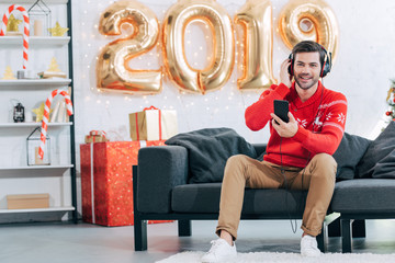 young smiling man listening music with headphones and smartphone at home with golden 2019 balloons for new year