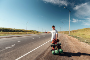 Travel man hitchhiking. Backpacker on road