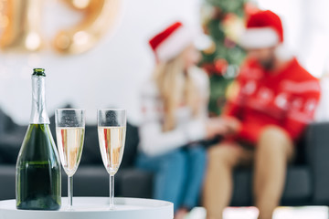 selective focus of champagne bottle and glasses for celebrating christmas, couple sitting behind