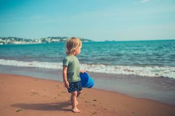 Little toddle ron the beach with a bucket